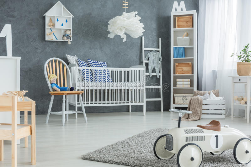 Boy room with cot. Grey boy room with white cot, bookcase and rug royalty free stock photo