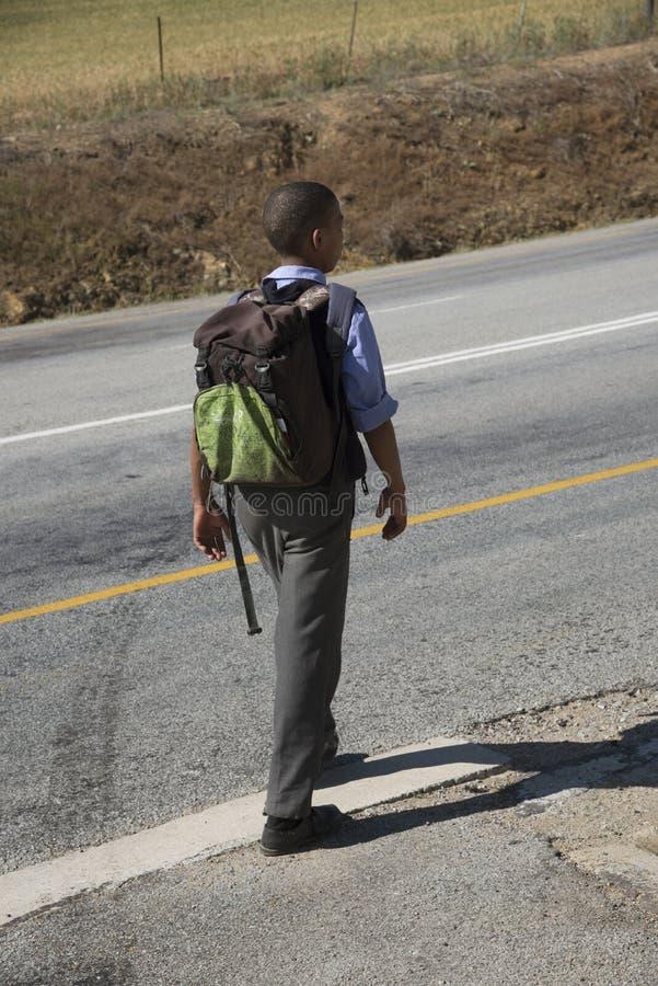 Boy with rucksack walking to school stock image