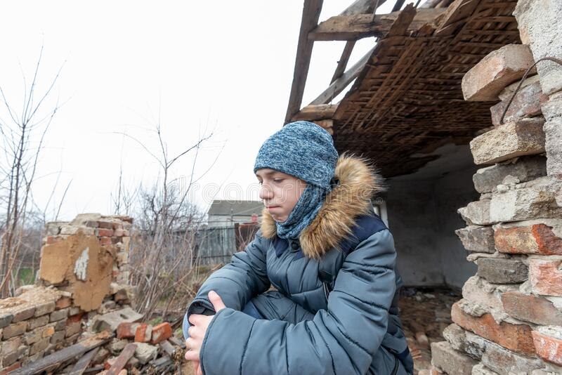 A boy in a ruined house, a teenager was left homeless as a result of military conflicts and natural disasters royalty free stock image