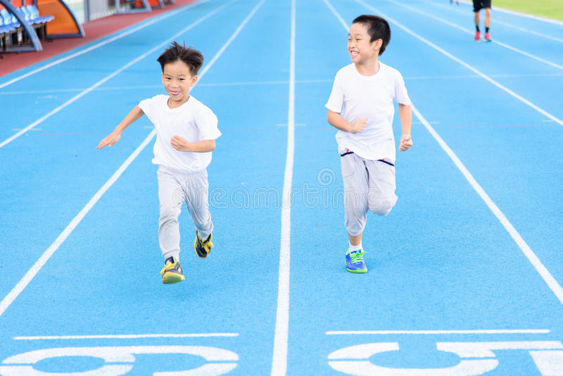 Boy runnin on blue track stock photos