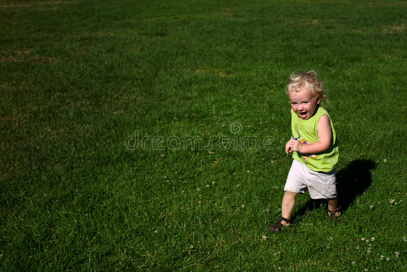 Boy Running on Grass in Park stock photography