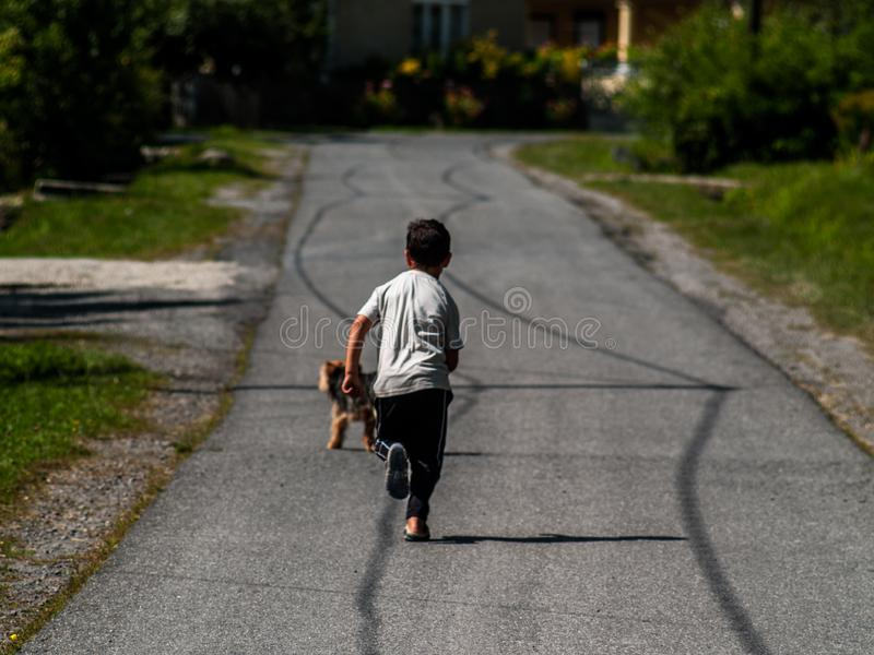 A boy running after his dog on a small street`s concrete road in a small sleepy village royalty free stock photo