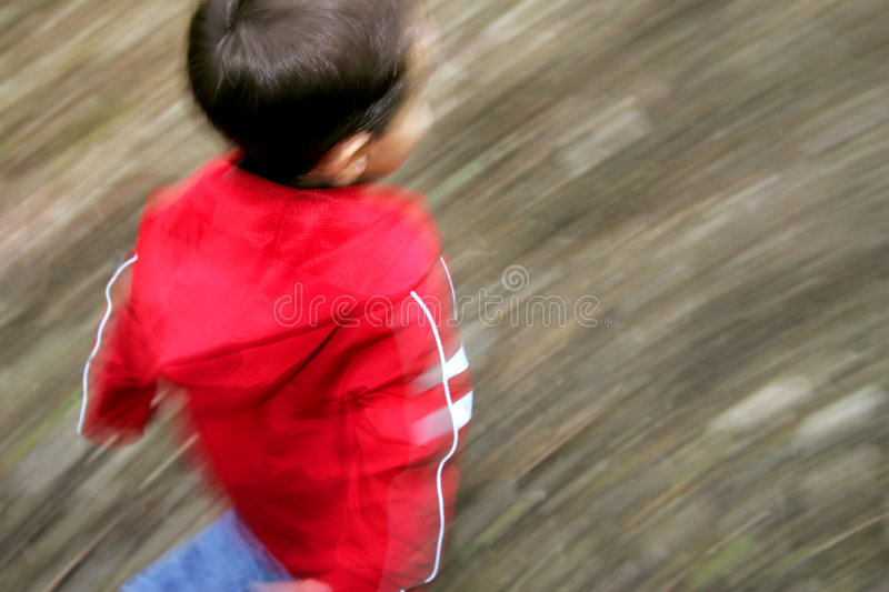 Boy running with motion blur. A young male running with panning motion blur abstract and artistic royalty free stock photo