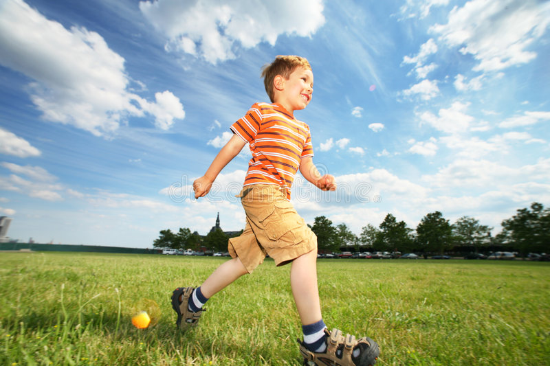 Boy running outdoors. Boy running on green grass field under beautiful blue sky with scenic white clouds stock photos