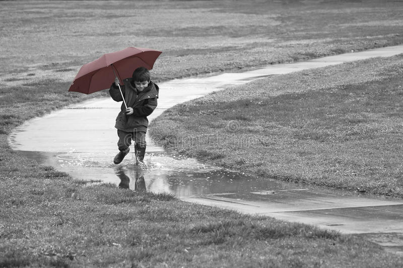 Boy running in the rain stock image