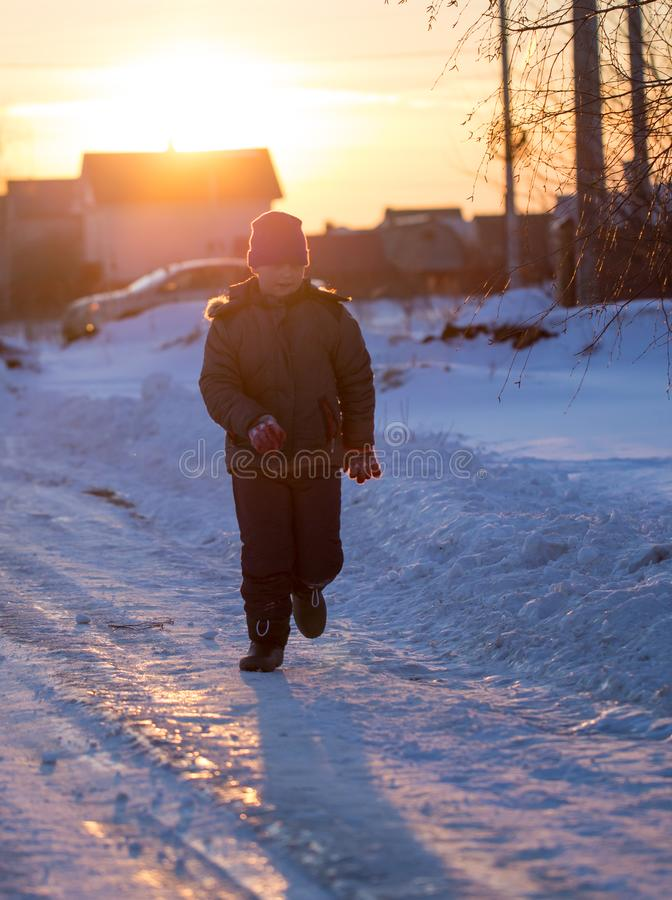 The boy is running on the road in winter at sunset royalty free stock photos