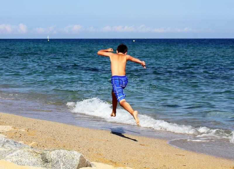 Boy running on the sea beach stock photos