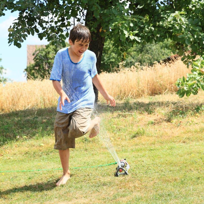 Boy running thru sprinkler stock photos