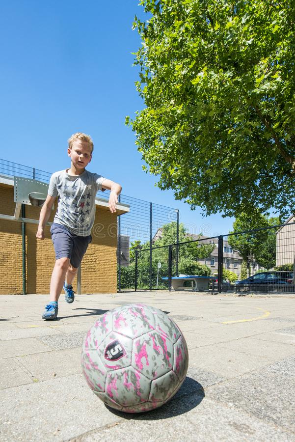 Boy at a Street soccer pitch stock photography