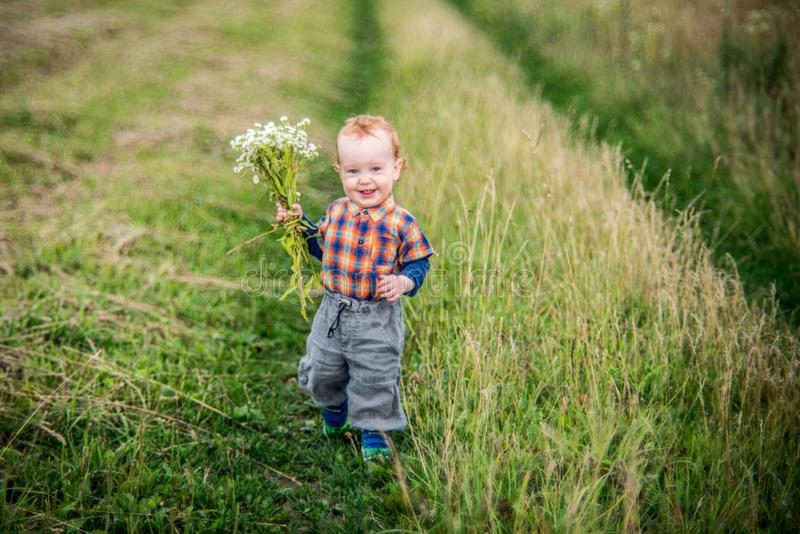 Boy running in wild field with flowers royalty free stock photos