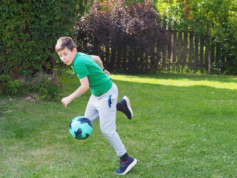 The boy runs with a soccer ball stock photo