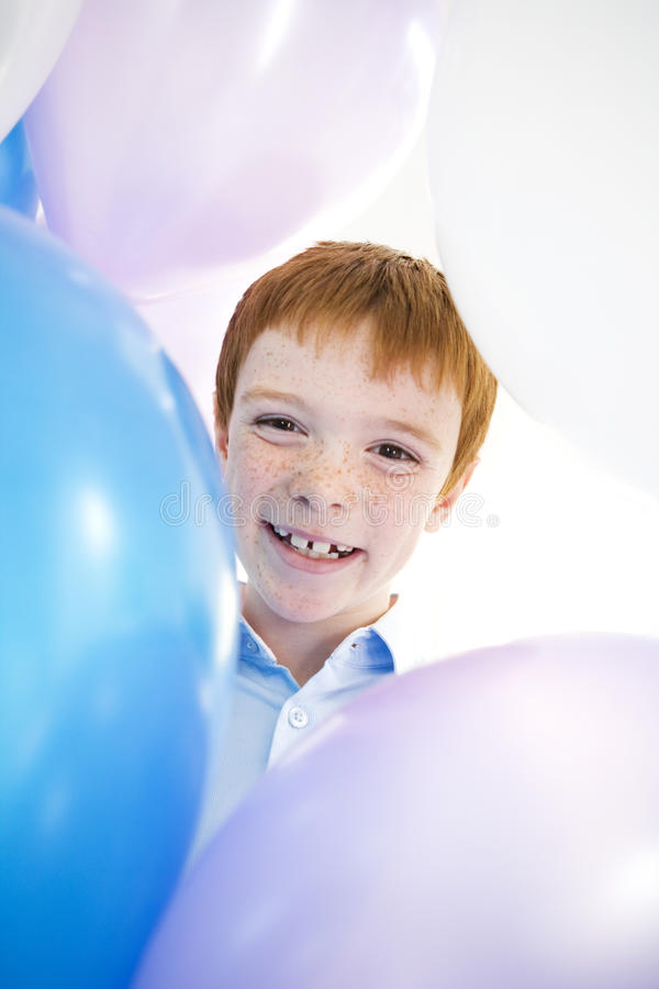 boy's face smiling framed by balloons stock photography