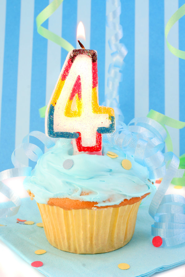 Boy's fourth birthday. Cupcake with blue frosting and decorative background royalty free stock image