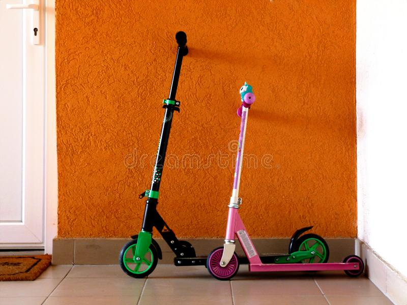 Boy and girl small colorful scooter leaning against the stucco wall next to white entrance door stock photo