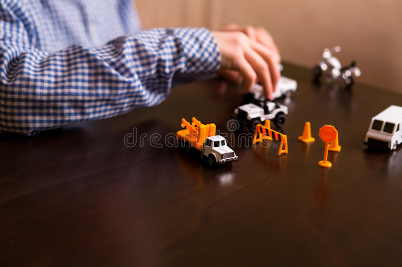 Boy's hand moves toy jeep. Child playing with toy cars. Imagination is power. Enjoy while you have time stock photography