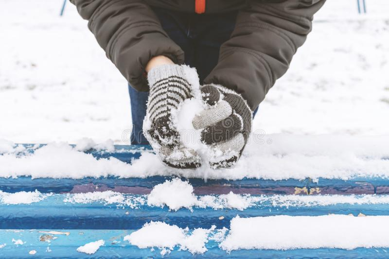Boy`s hands wearing mittens, gloves sculpts snowballs, outdoor winter activities, sports concept royalty free stock photography
