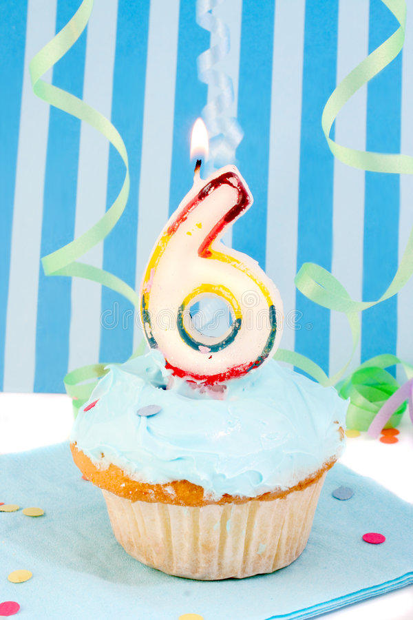 Boy's sixth birthday. Cupcake with blue frosting and decorative background royalty free stock image