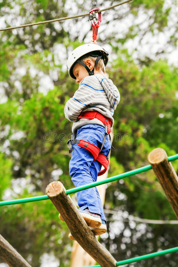 Boy in safe equipment on the rope-ladder in adrenalin park stock image