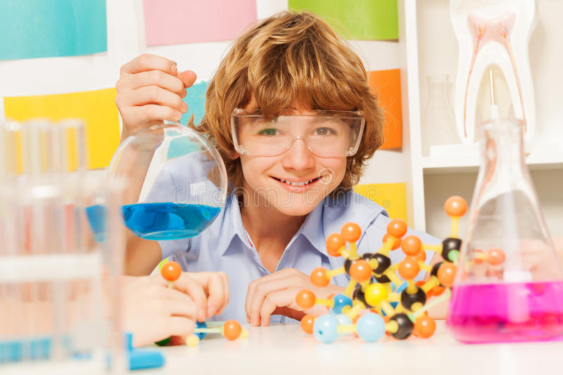 Boy in safety goggles holding flask at the lab stock photography