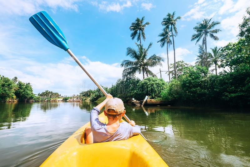 Boy sailing in canoe boat on tropical lagoon royalty free stock image