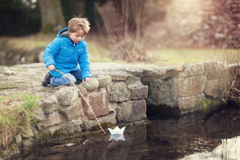 Boy sailing a paper boat royalty free stock image