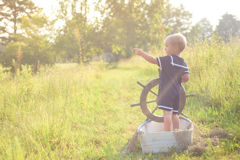 Boy in sailor suit in boat on grass royalty free stock photos