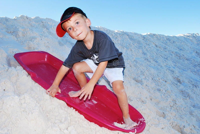 Boy sand sledding stock images