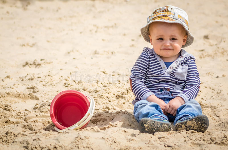 Boy in a sandpit. Cute little boy sitting in a sandpit in an outdoor playground royalty free stock images