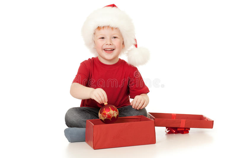Boy in Santa hat opening christmas gift in red box stock photo