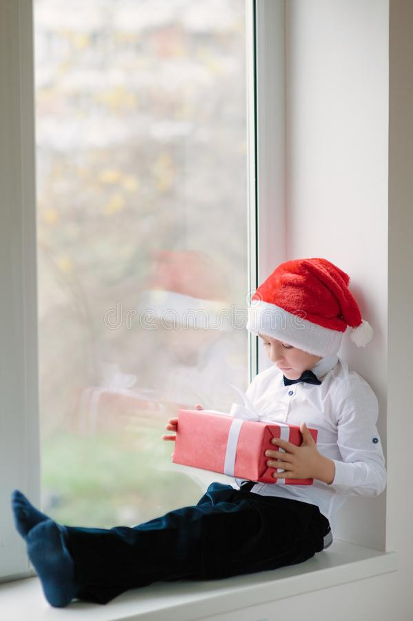 Boy in santa hat sit near the window and holds gifts royalty free stock photos