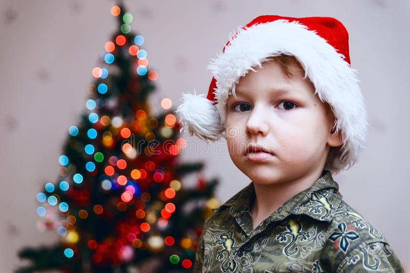 Boy in Santa`s Cap on Christmas tree background. Looking at camera stock images
