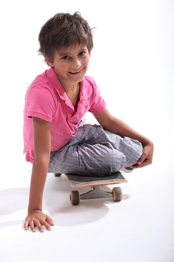 Boy sat on skateboard royalty free stock photos