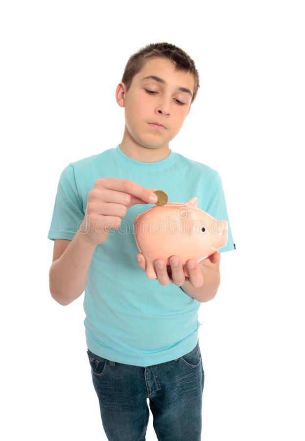 Boy saving coins for a rainy day. A boy puts spare change coins into a money box stock photo