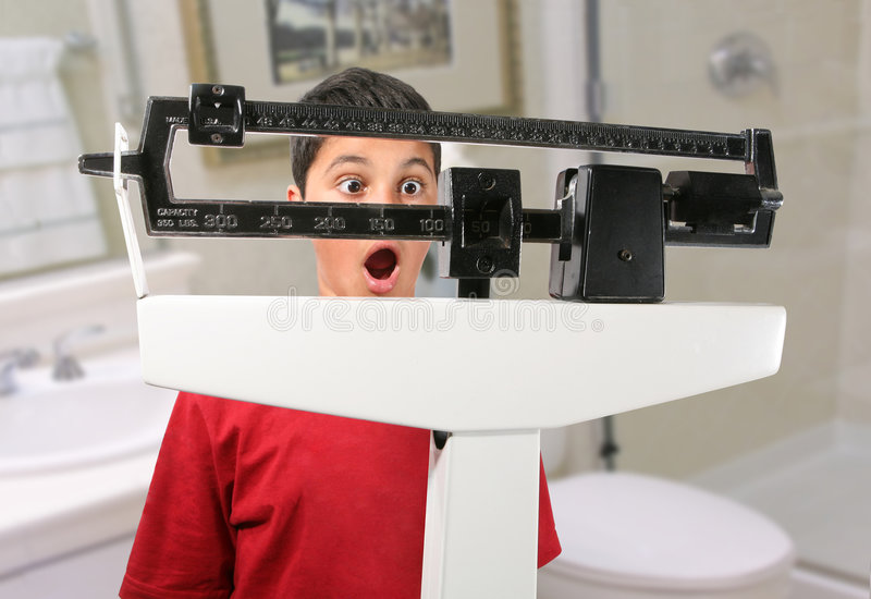 Boy on Scale. A boy on a scale looking surprised at his weight