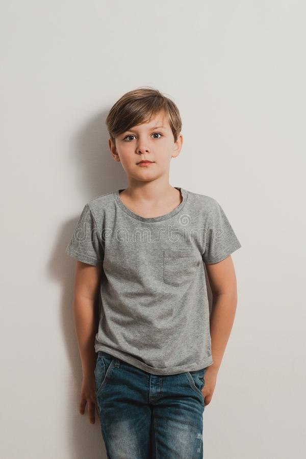 A boy with scared face by the white wall, grey shirt, jeans royalty free stock images