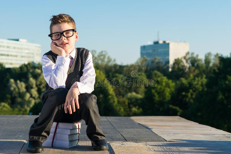 The boy from school in glasses sits on textbooks royalty free stock image