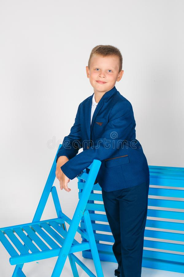 Boy schoolboy in fashionable school clothes with a school bag and a book. On a white background stock photos