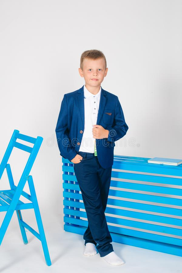Boy schoolboy in fashionable school clothes with a school bag and a book. On a white background stock images