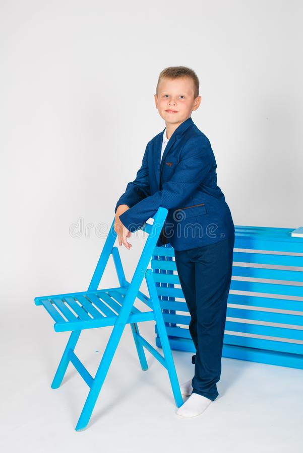 Boy schoolboy in fashionable school clothes with a school bag and a book. On a white background royalty free stock image