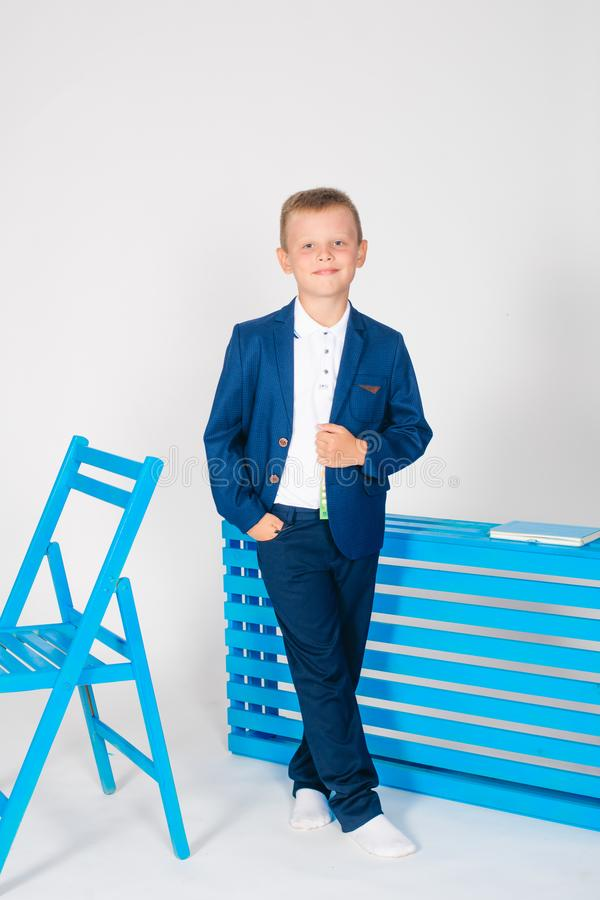 Boy schoolboy in fashionable school clothes with a school bag and a book. On a white background royalty free stock photo