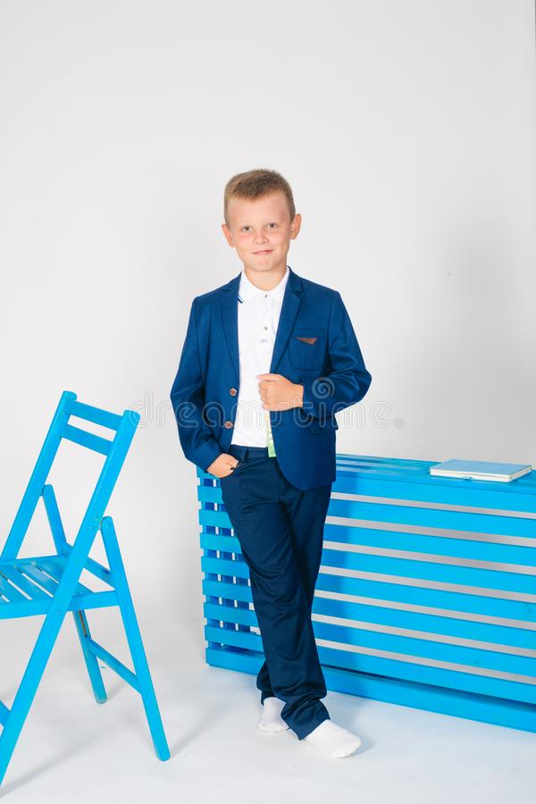 Boy schoolboy in fashionable school clothes with a school bag and a book. On a white background royalty free stock photos