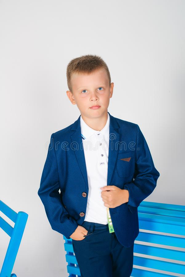 Boy schoolboy in fashionable school clothes with a school bag and a book. On a white background stock photography