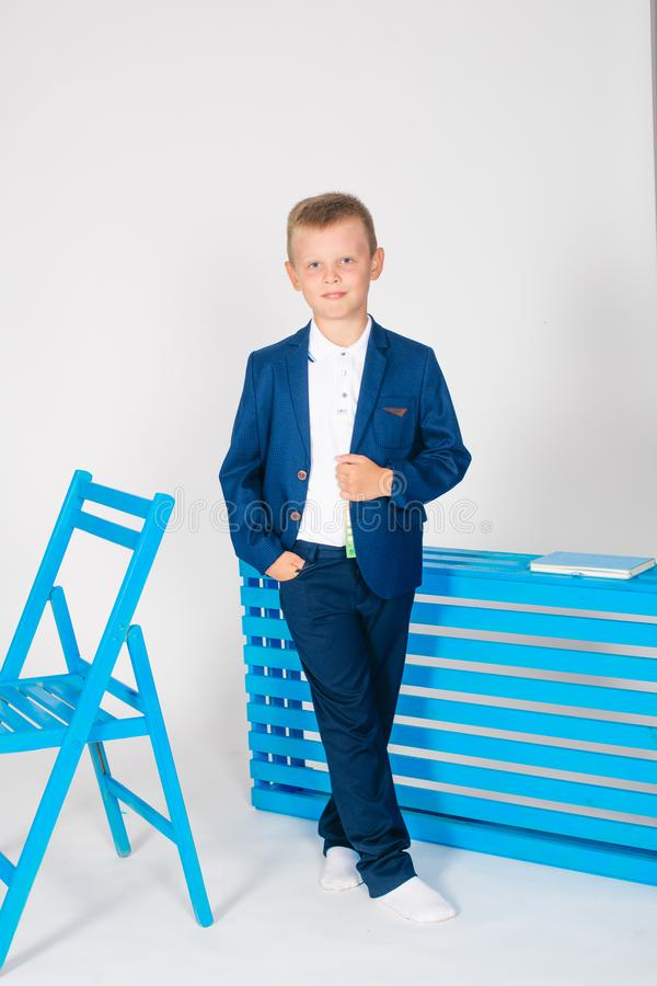 Boy schoolboy in fashionable school clothes with a school bag and a book. On a white background stock photo
