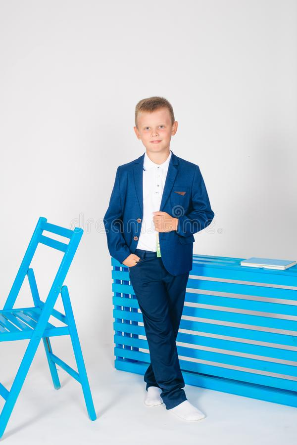 Boy schoolboy in fashionable school clothes with a school bag and a book. On a white background royalty free stock images