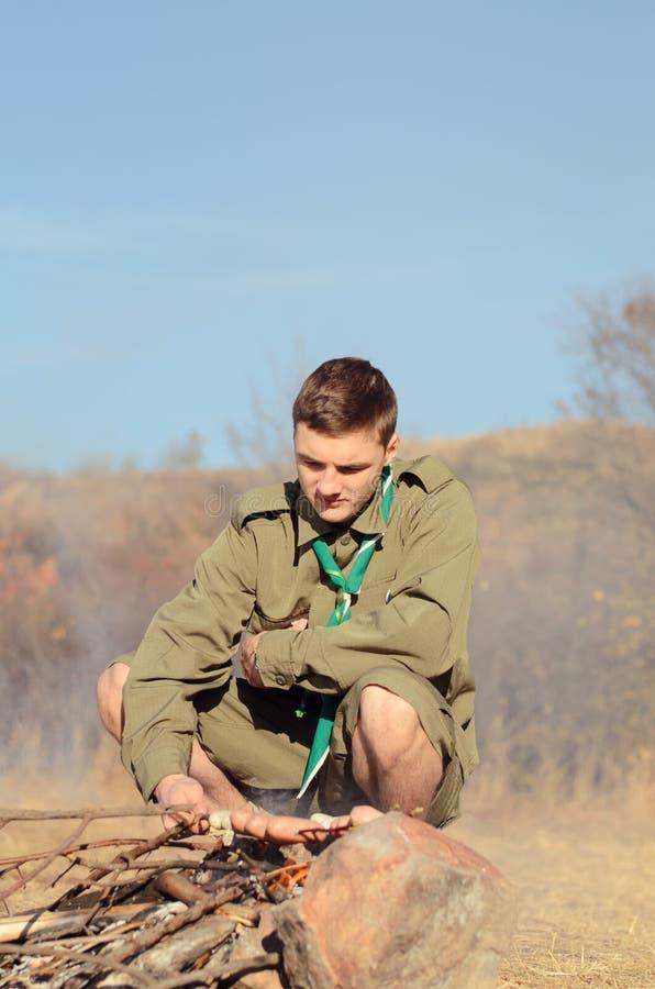 Boy scout Cooking Sausages en el palillo sobre hoguera imágenes de archivo libres de regalías