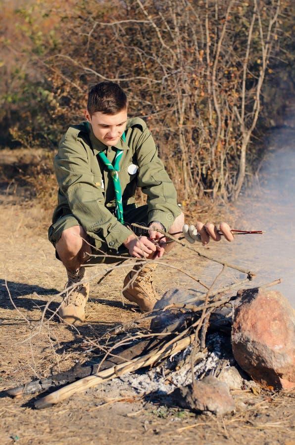 Boy scout Cooking Sausages en el palillo sobre hoguera foto de archivo libre de regalías