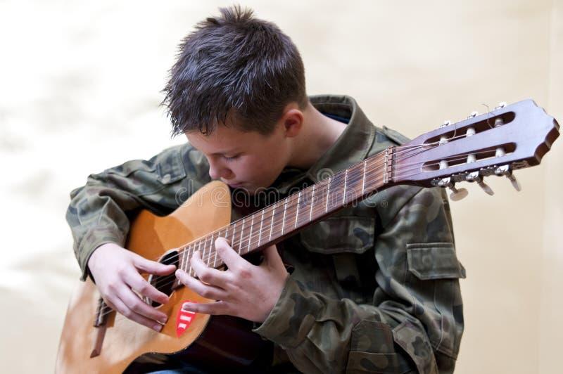 Boy scout guitar. A teenage boy scout playing a classic guitar stock photos
