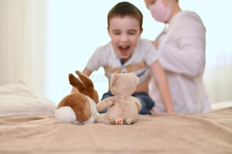The boy screams at the examination at the doctor. stock images