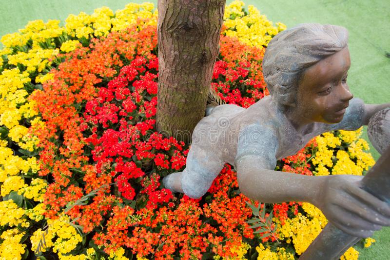 A boy sculpture among red and yellow flowers at Princess Maha Chakri Sirindhon Herbal Garden - Rayong, Thailand. A boy sculpture among red and yellow flowers at stock images