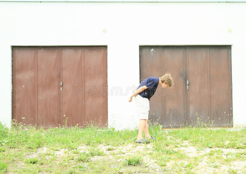 Boy searching for keys. Little boy - kid searching for keys in front of garages royalty free stock image
